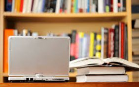 Laptop with pile of books