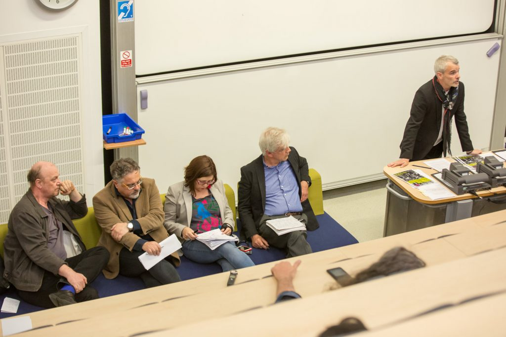 Standing Seminar in Critical Theory Photo: 4 Presenters sat in a line listening to a fifth presenter present to a lecture theatre