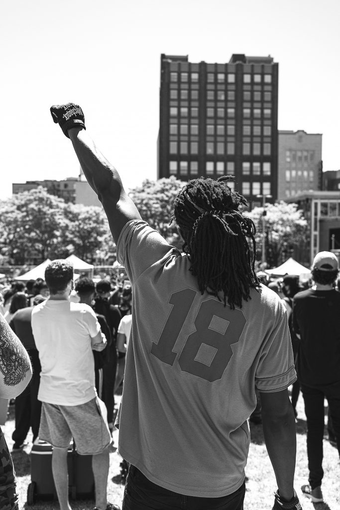 monochrome photo of black man with dreadlocks, wearing a white tshirt and raising left fist in the air with crowd in the background